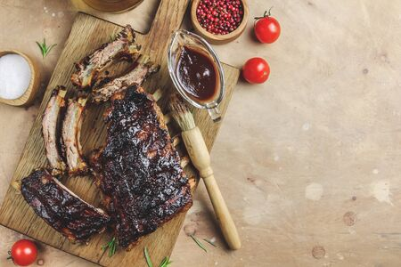 Delicious barbecued ribs seasoned with bbq sauce on rustic wooden chopping board. Top view. Selective focus Foto de archivo - 129246533