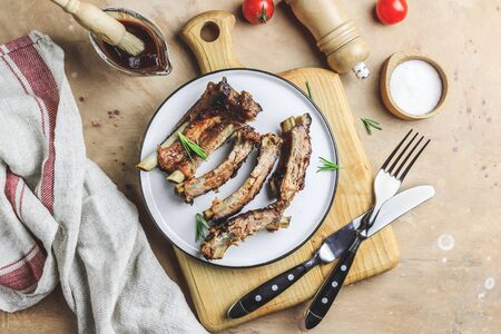 Delicious barbecued ribs seasoned with bbq sauce on rustic wooden chopping board. Top view Foto de archivo - 129246586
