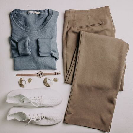Woman fashion clothes set flatlay. Blue pullover, brown pants, white sneakers, watch, wooden earrings on white background. Flat lay. Top view