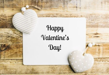 Rustic Valentines day background with toy hearts over wooden table. Card with text. Top view. Flat lay