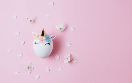 Easter eggs in the form of a unicorn on pink background. Happy Easter time. Creative Easter decoration. Copy space. Flat lay 免版税图像