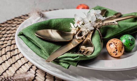 Easter table setting. Empty plates with green linen napkin and golden cutlery on concrete Archivio Fotografico
