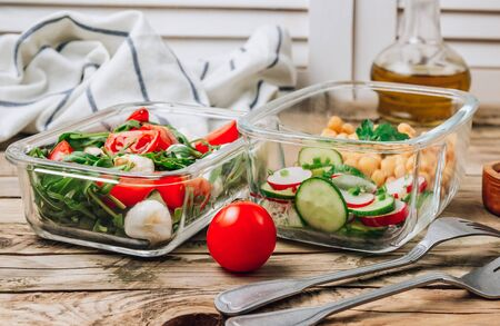 Healthy meal prep containers with chickpeas and spring salad with cucumbers, radish and chives and containers with caprese salad with arugula. Healthy lunch in glass containers. Zero waste concept. 스톡 콘텐츠 - 146139800