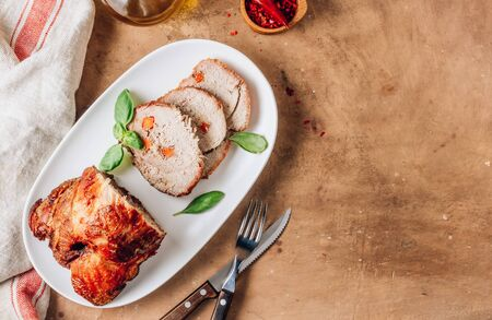 Roasted sliced pork ham on a white plate on a beige rustic Stock Photo