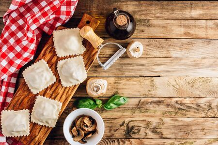 Homemade fresh Italian ravioli pasta with mushrooms on rustic wooden background. Top view with copy space