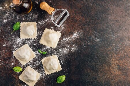 Homemade fresh Italian ravioli pasta with mushrooms on dark background. Top view with copy space