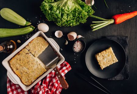 Zucchini casserole on dark background. Dietary, low-calorie, healthy food. Homemade Casserole from squash with chicken and eggs. Top view