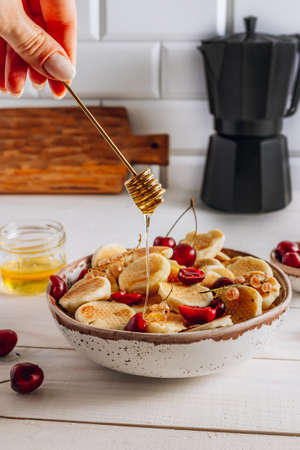 Trendy home breakfast with tiny pancakes in a bowl with honey and cherries on a white wooden table. Honey spoon in female hands. Selective focus. Vertical photo Фото со стока
