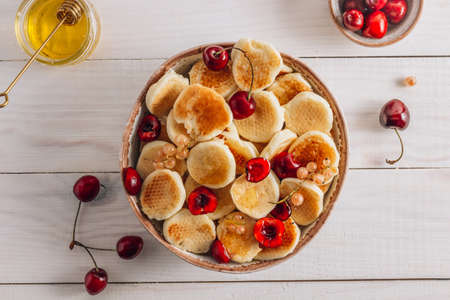 Trendy home breakfast with tiny pancakes in a ceramic bowl with honey and cherries on a white wooden table. Top view