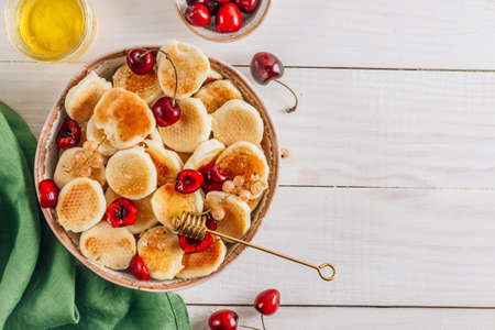 Trendy home breakfast with tiny pancakes in a bowl with honey and cherries on a white wooden table with a green napkin. Top view with copy space Фото со стока