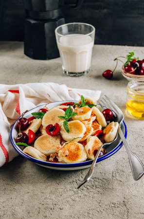 Trendy home breakfast with tiny pancakes in a bowl with honey and cherries on a concrete table. Selective focus. Vertical photo