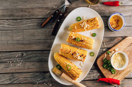 Grilled spicy corn cobs on white plate on rustic wooden background