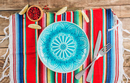 Festive Mexican table setting. Plate and cutlery with colorful napkin on rustic wooden background. Flat lay.