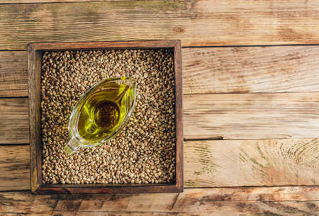 Hemp oil n a glass bowl and hemp seeds on rustic wooden background.