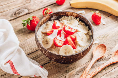 Quinoa porridge with coconut milk and fresh strawberries in a coconut bowl wooden rustic background. Healthy Lactose and Gluten Free Breakfast.