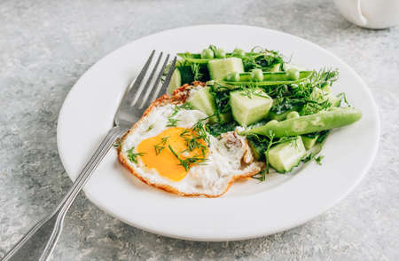 Healthy breakfast with eggs and cucumber salad with coffee on light gray background. Flat lay. Minimal concept