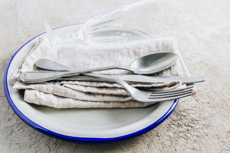 Gray aluminum plate, vintage cutlery, glass and linen napkin on light gray concrete background. Table setting for menu, layout, place for text , recipe background Reklamní fotografie