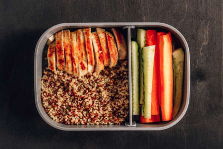 Healthy meal prep containers with quinoa, chicken and and sticks of cucumber and carrots on black wooden background. Healthy lunch at work. Take away concept.
