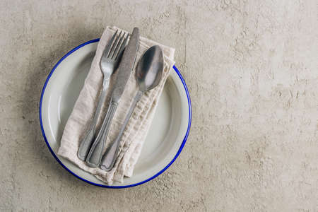 Gray aluminum plate, vintage cutlery and linen napkin on light gray concrete background. Table setting for menu, layout, place for text , recipe background