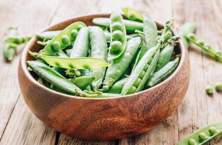 Organic green peas in wooden bowl on wooden background. Reklamní fotografie
