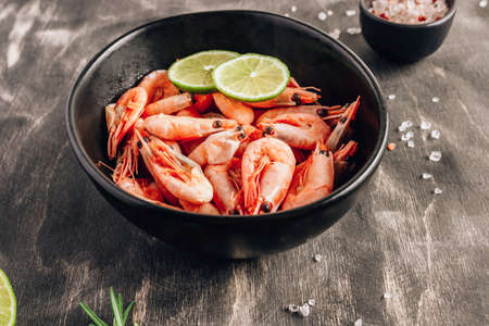 Top view of bowl with boiled shrimps with lime in black bowl on dark background.