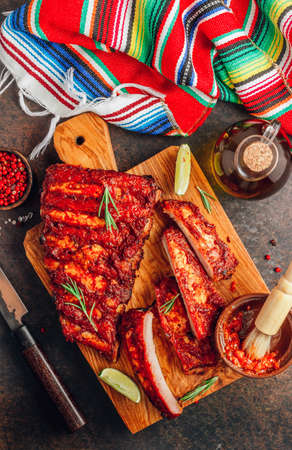 Mexican barbecued ribs seasoned with a spicy tomato sauce served on a wooden chopping board on a dark background. Reklamní fotografie