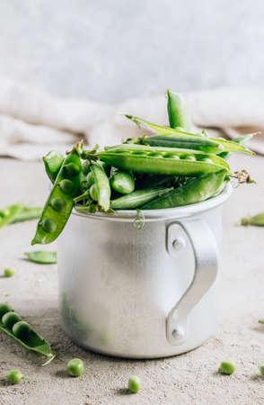 Organic green peas in aluminum mug on light gray background.