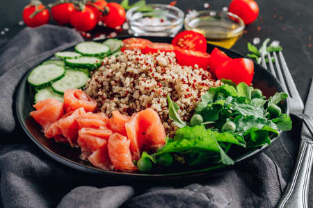 Salmon Poke bowl. Raw fish salad with quinoa, cucumber, tomato and arugula. Asian trendy food on black wooden background.