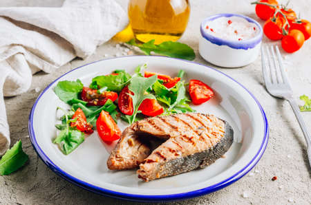 Grilled Pink salmon steak and salad on concrete background. Healthy food concept.