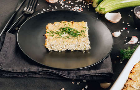 Zucchini casserole on dark background. Dietary, low-calorie, healthy food. Homemade Casserole from squash with chicken and eggs.