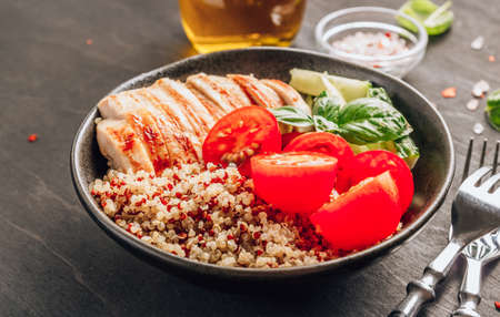 Healthy salad bowl with quinoa, tomatoes, chicken, cucumber and basil on black wooden background. Superfoods. Reklamní fotografie