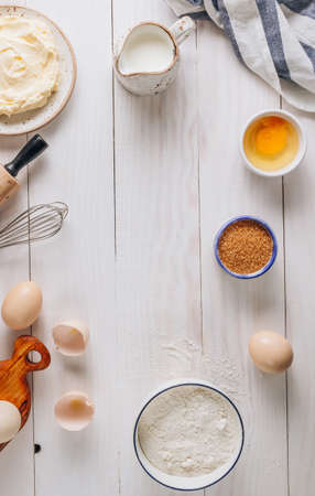 Ingredients for baking and Breakfast with eggs, flour, sugar, milk and butter on a white wooden background. Delicious and healthy food. Flat lay.