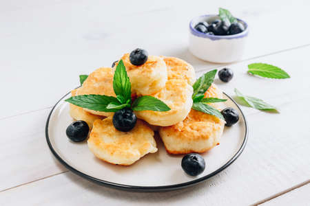 Trandy food - fluffy mini pancakes with blueberries and mint on a white wooden background. Reklamní fotografie