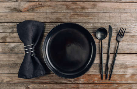 Black plate, cutlery and napkin on rustic wooden background. Table setting.