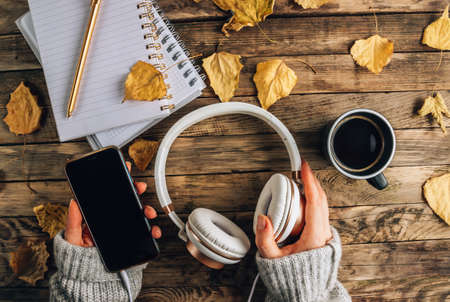 Headphones with autumn dry leaves, cuo of coffee and notepads on rustic wooden background
