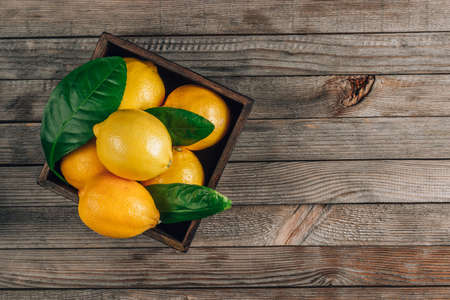 Fresh lemons in an old box with leaves on rustic wooden background Reklamní fotografie