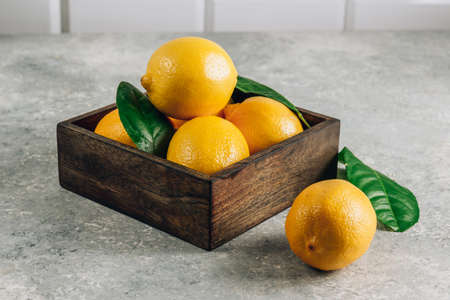 Fresh lemons in an old box with leaves on light gray background