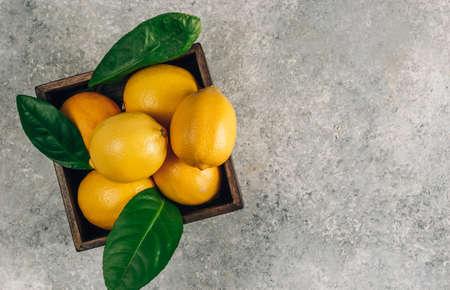Fresh lemons in an old box with leaves on light gray background. Reklamní fotografie