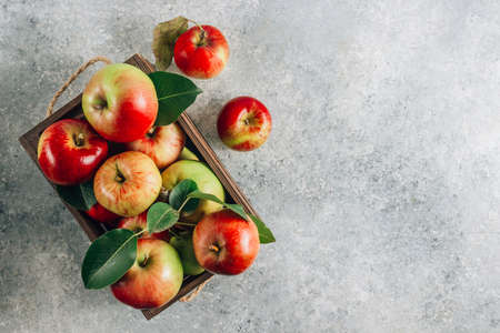Fresh organic green and red apples in the wooden box. On light gray background.