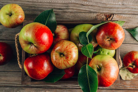 Fresh organic green and red apples in the wooden box. On rustic wooden background.