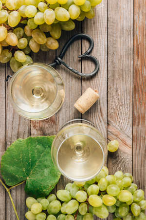 Two glasses of white wine and grape on vintage wooden table Reklamní fotografie