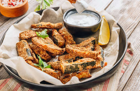 Crispy zucchini sticks with yogurt dip on rustic wooden background. Healthy snack Reklamní fotografie