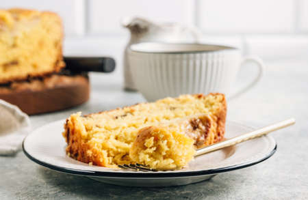 Loaf of banana bread on a wooden cutting board with cup of tea on light gray table.
