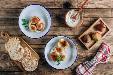 Healthy snack wholegrain rice crispbread crackers, figs and ricotta cheese on rustic wooden background.