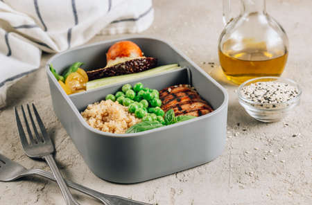 Healthy lunch in plastic containers with quinoa and chicken.
