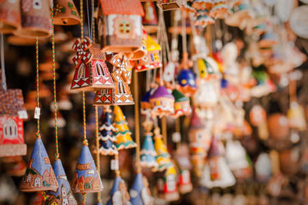 Souvenir ceramic bells and toy houses at the market, local national craft Stock Photo
