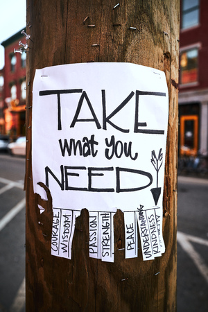 street wise: Street art paperwork at a wooden street light asking to take what you need