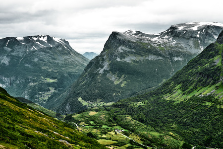 Close-up view of the mountains in western Norway with small villages and town at the bottom of the valley and summits covered with snow