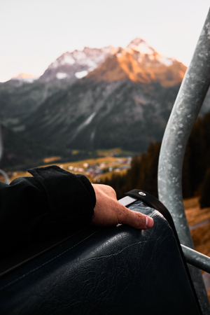 point of view from the chair lift over the valley and mountains with an arm in the foreground during sunset in Austria