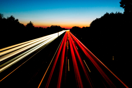 Long exposure image of the highway A2 in Germany Gelsenkirchen with red and white light trails and a colorful sunset in the background